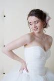Sposa sorridente felice in vestito bianco vicino alla parete Immagini Stock Libere da Diritti