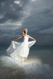 Sposa splendida che sta e che posa sotto le nuvole minacciose alla s Fotografie Stock