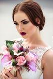 Sposa splendida con trucco di modo e acconciatura in un vestito da sposa di lusso fotografia stock