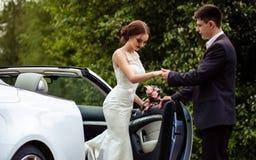 Sposa splendida con trucco di modo e acconciatura in un vestito da sposa di lusso con lo sposo bello vicino all'automobile bianca immagini stock