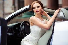 Sposa splendida con trucco di modo e acconciatura vicino al vestito da sposa di lusso vicino all'automobile bianca del cabriolet fotografia stock