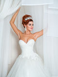 Sposa splendida in una stanza elegante bianca Fotografia Stock