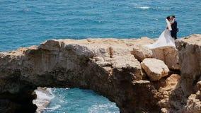 Sposa su un ponte di pietra nel baciare del mare video d archivio