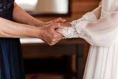 Sposa sul giorno delle nozze che tiene le sue mani del ` s della madre una donna anziana giudica la sua giovane figlia sposata immagine stock