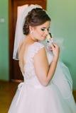 Sposa timida in vestito bianco che posa, tenente piccolo boutenniere sveglio e esaminante la sua spalla fotografia stock