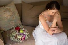 Sposa triste che si siede dal mazzo sul sofà a casa Fotografia Stock