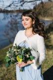 Sposa in un vestito blu con il mazzo nel lago Fotografia Stock