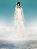 Sposa in vestito bianco da nozze che sta su una nuvola immagine stock