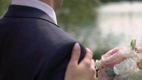 Sposa in vestito da sposa splendido che viene allo sposo bello e che si abbraccia archivi video