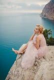 Sposa in vestito da sposa che sta su una roccia Fotografia Stock