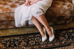 Sposa in vestito da sposa di seta sveglio e scarpe alla moda che si siedono su un sofà allo spogliatoio che aspetta la cerimonia Fotografia Stock