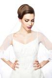 Sposa in vestito da sposa e velo confuso modestamente. Fotografie Stock