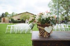 Sposi che si siedono sulle sedie bianche del woodem in un giardino alla cerimonia di sarchiatura fotografie stock libere da diritti