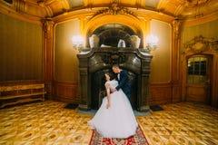 Sposo alla moda elegante che immerge la sua moglie affascinante, posante nell'interno ricco di vecchio palazzo classico immagini stock