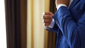 Sposo alla moda nei gemelli d'uso del vestito di lusso blu vicino su video d archivio