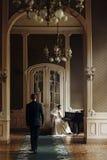 Sposo bello alla moda elegante che abbraccia la sua sposa splendida mentre fotografie stock libere da diritti
