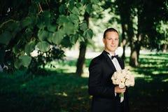 Sposo bello dei giovani che posa fuori in natura Fotografie Stock Libere da Diritti