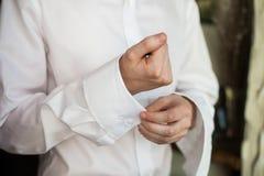 Sposo bello dell'uomo che abbottona camicia bianca alla moda elegante mentre p Fotografie Stock