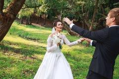 Sposo bello felice e bella sposa in vestito bianco che ridono e che ballano nel parco fotografie stock libere da diritti