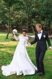 Sposo bello felice e bella sposa in vestito bianco che ridono e che ballano nel parco fotografia stock