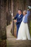 Sposo che apre il champagne al giorno delle nozze immagine stock