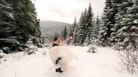 Sposo che fila sposa felice che la tiene e che fila in sue mani nella foresta attillata dell'albero di abete del tempo della neve video d archivio
