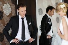 Sposo che guarda la sua sposa ottenere pronta immagine stock
