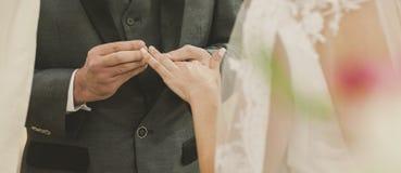 Sposo che mette alleanza durante la cerimonia religiosa fotografie stock