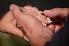Sposo che mette anello sulla barretta delle spose Immagini Stock