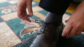 Sposo che mette le sue scarpe di nozze Mani dello sposo di nozze che si preparano nel vestito archivi video