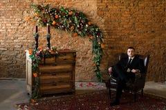 Sposo che si siede con confidenza in una grande sedia fotografie stock libere da diritti