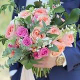 Sposo che tiene un bello mazzo nuziale Il mazzo di nozze delle rose della pesca da David Austin, rosa della unico testa è aumenta fotografia stock libera da diritti