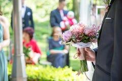 Sposo che tiene un mazzo di cerimonia nuziale Fotografia Stock