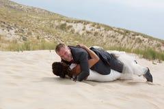Sposo con i vestiti d'uso della sposa che si trovano sulla spiaggia Immagini Stock