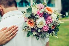 Sposo dell'abbraccio della sposa con il mazzo di nozze Fotografie Stock Libere da Diritti