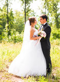 Sposo e sposa in un parco Mazzo nuziale di cerimonia nuziale dei fiori Fotografie Stock Libere da Diritti
