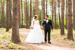 Sposo e sposa in un parco Mazzo nuziale di cerimonia nuziale dei fiori Immagini Stock