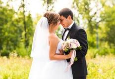 Sposo e sposa in un parco Mazzo nuziale di cerimonia nuziale dei fiori Immagine Stock