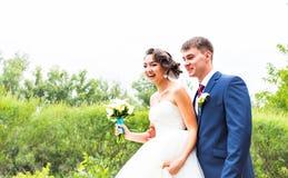 Sposo e sposa in un parco Vestito da cerimonia nuziale Mazzo nuziale di cerimonia nuziale dei fiori Fotografie Stock Libere da Diritti