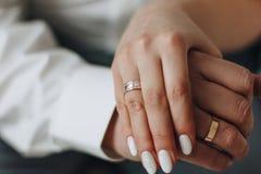 Sposo ed e mani della sposa con gli anelli Fotografia Stock