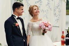 Sposo felice bello e bella sposa bionda in vestito bianco a Fotografia Stock