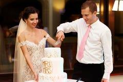 Sposo felice delle coppie e bella sposa che tagliano nozze deliziose Immagine Stock Libera da Diritti