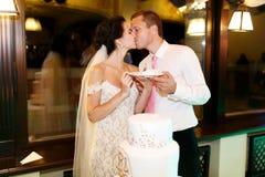 Sposo felice delle coppie e bella sposa che tagliano nozze deliziose Fotografie Stock