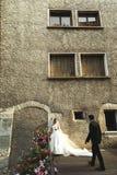 Sposo sicuro bello che si avvicina alla bella sposa vicino al vecchio franco Fotografie Stock Libere da Diritti