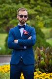Sposo sicuro bello in vestito blu ed occhiali da sole che posano dentro Immagine Stock