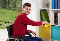 Sposobny niepełnosprawny mężczyzna wyciera pył zdjęcie stock