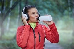 Sposrtswoman drinking isotonic drink. Front portrait of beautiful sportswoman drinking isotonic drink Royalty Free Stock Images