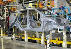 Spot contact welding of bodies of cars at automobile plant. Industry Stock Photos