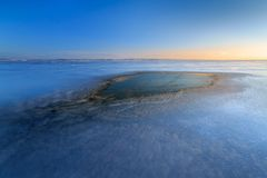 Spot dawn on a frozen lake Stock Images