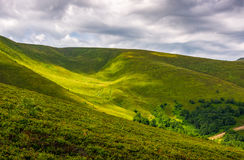 Spot of light on green hillside on overcast day. Beautiful summer nature background in mountains Stock Photo
